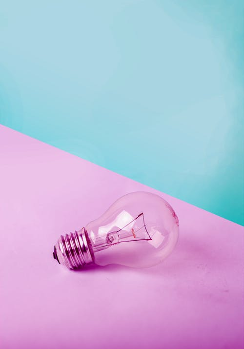 Lightbulb on pink and blue paper illustrating how creating a customer avatar can help make your marketing easier.
