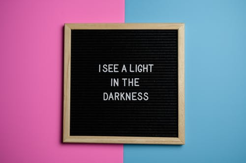 """Board with writing """"I see a light in the darkness"""" on pink and blue background illustrating how creating a customer avatar can help make your marketing easier."""